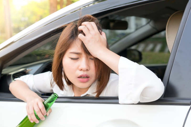 Driver leaning out car with beer in hand