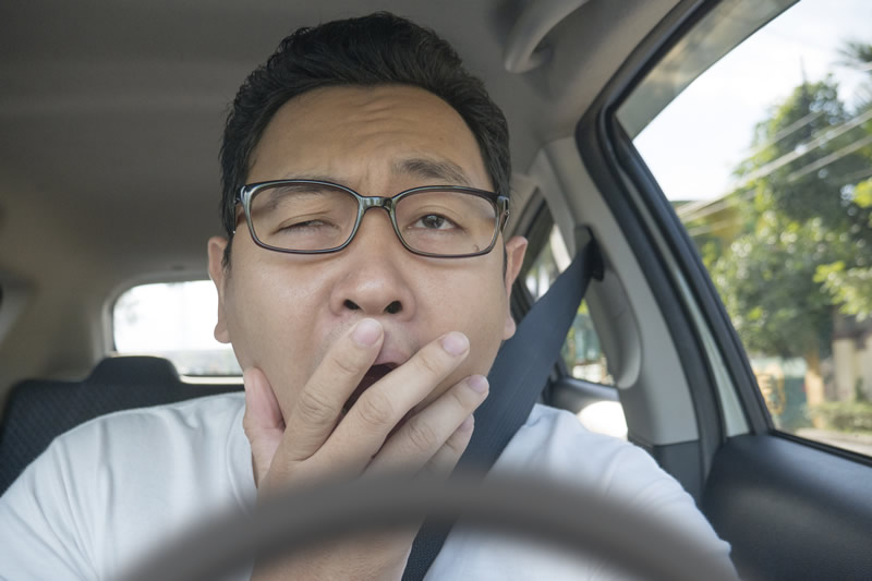 Man yawning behind wheel of car