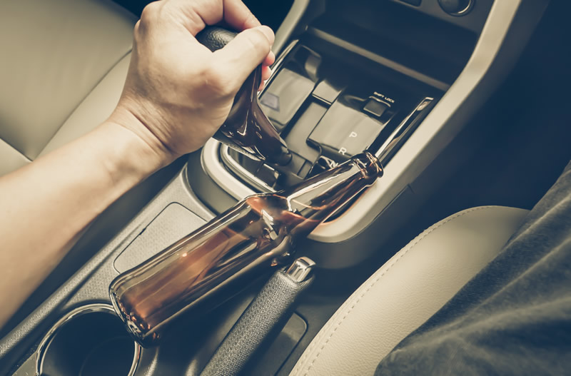 Beer bottle in car as driver shifts into gear