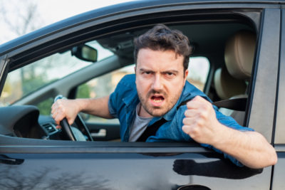 Angry man driving with road rage